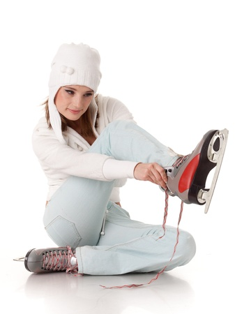 Beautiful young woman in winter clothes with skates  on a white background. Winter sports. photo