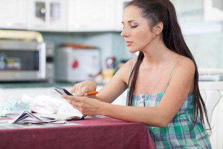 The young pregnant woman plans the family budget on the house kitchen. photo