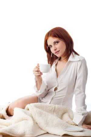 Young woman with  cup of coffee sits on warm plaid on a white background. photo