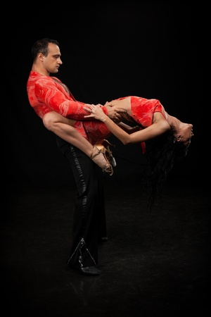 Dancing young couple on a black background. photo