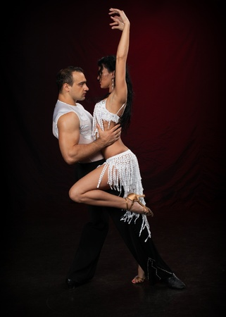 Dancing young couple on a dark background. photo