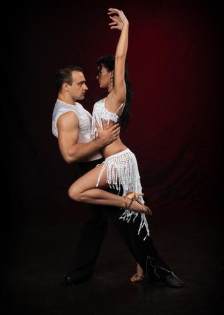 Dansen jong koppel op een donkere achtergrond. Stockfoto
