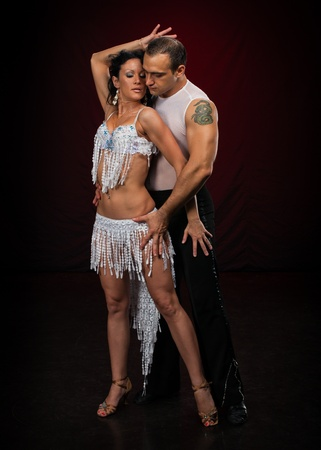 bailarines de salsa: Pareja de baile joven sobre un fondo oscuro.