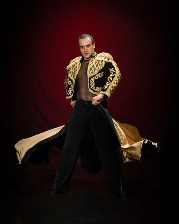 Male dancer dressed as a matador on a dark background. photo