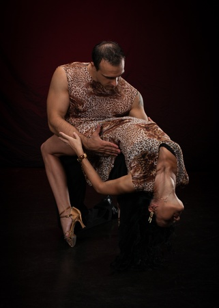 rhythmical: Dancing young couple on a dark background.