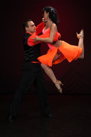 Dancing young couple on a dark background.