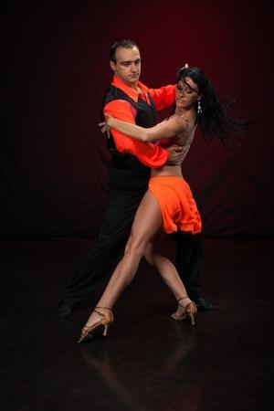 Dansende jonge paar op een donkere achtergrond.