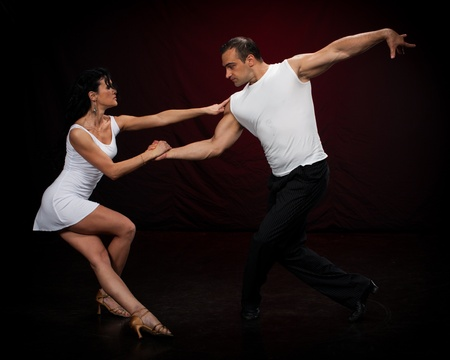 salsa dance: Dancing young couple on a dark background.
