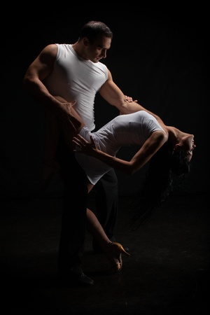 Dancing young couple on a black background.
