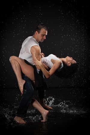 Young couple dancing in water under rain on a black background.  Modern dances. Stock Photo