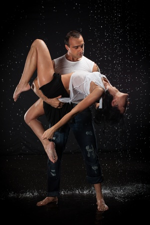 Young couple dancing in water under rain on a black background.  Modern dances. photo
