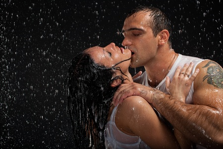 Young loving couple under rain on a black background.