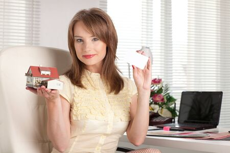 Businesswoman with blank business card and with model of house sits at the table at office. photo