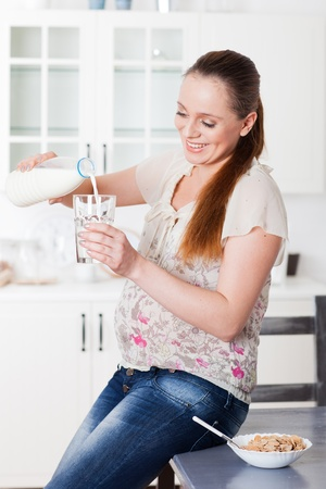 Pregnant woman drinks the milk on the house kitchen. photo