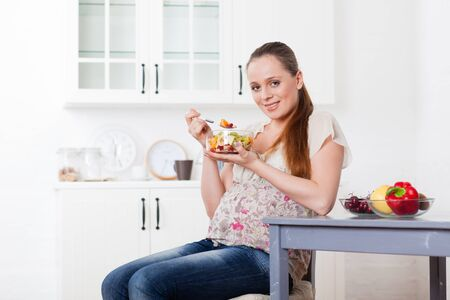 Pregnant woman eats fruit salad on the house kitchen.