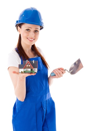 Young woman in  coverall with trowel and model of house on a white background. Female construction worker. photo