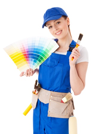 Jonge vrouw in overall met een kleur gids en penselen op een witte achtergrond.