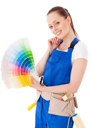 Young woman in  coverall with a color guide and paintbrushes on a white background. photo