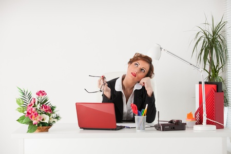 Young businesswoman sits at the table at the office. photo
