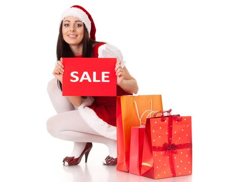 Pretty young woman in Santas suit with shopping bags on a white background. photo
