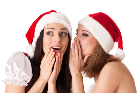 Two young women in Santa costume on a white background. Female secrets. photo