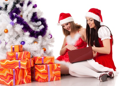 Two girlfriends with laptop and gifts sit near Christmas tree on a white background. Stock Photo - 11923636