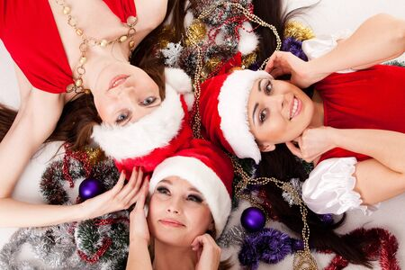 Happy girlfriends lying with  Christmas decoration. photo