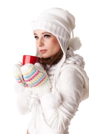 warm clothes: Giovane bella donna in abiti invernali caldi con tazza rossa su sfondo bianco.
