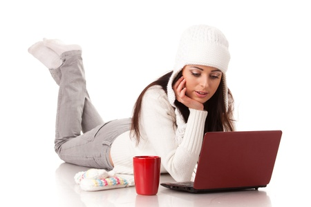 Beautiful young  woman in winter clothes with laptop lies on a white background. photo