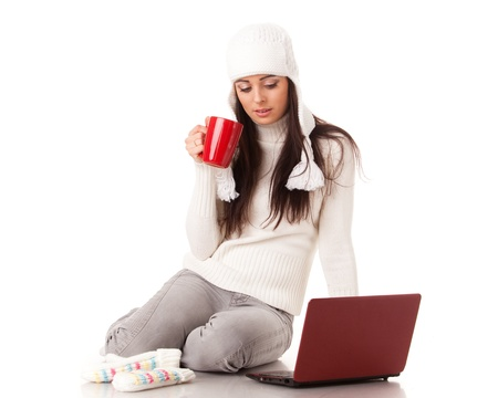 Beautiful young  woman in winter clothes with laptop sits on a white background. photo