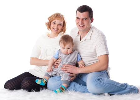 Young parents with their sweet  baby on a white background. Happy family. Stock Photo - 12024586