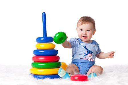 Zoete kleine baby met speelgoed op een witte achtergrond. Stockfoto