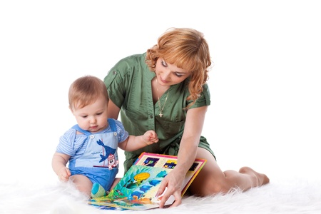 Mother with small baby reads the book on a white background.