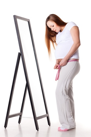 Pregnant woman stands before a mirror and measures her belly on a white background. photo
