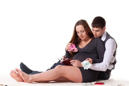 The young pregnant woman with her husband plan the family budget on a white background. photo