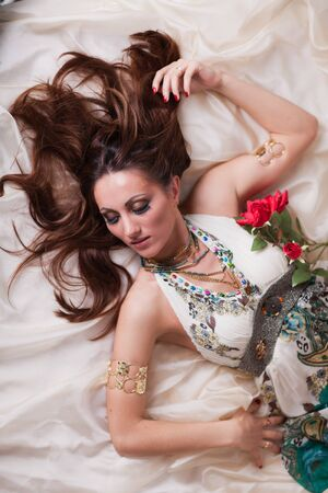Young beautiful woman with roses lies on the bed. photo