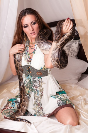 Young beautiful woman with snake sits on the bed. photo