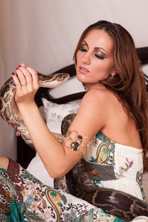 Young beautiful woman with snake sits on the bed. Stock Photo - 12106200
