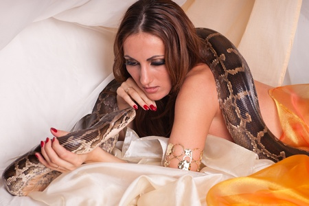 tempter: Young beautiful woman with snake lies on the bed.