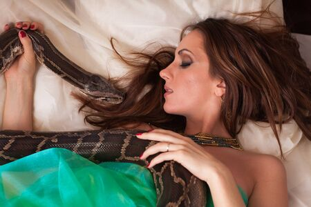 Young beautiful woman with snake lies on the bed. photo