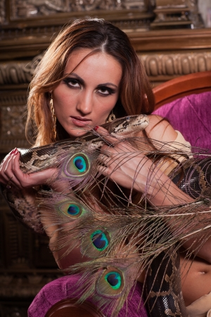 Young beautiful woman with snake sits on the sofa. photo