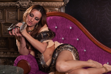 the tempter: Young beautiful woman with snake sits on the sofa.