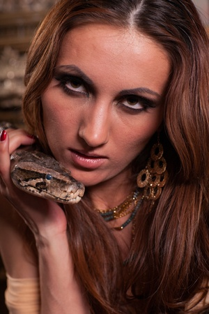 tempter: Portrait of young beautiful woman with snake.