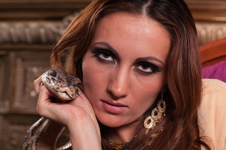 Portrait of young beautiful woman with snake. photo