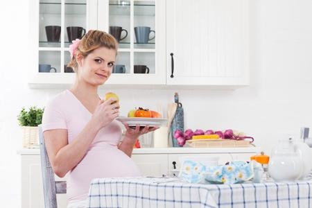 Mooie zwangere vrouw met vers fruit op het huis keuken.