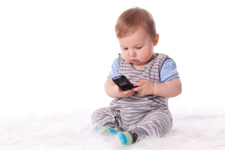 Sweet small baby with mobile phone on a white background. photo