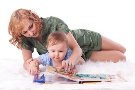 Moeder met kleine baby leest het boek op een witte achtergrond. Stockfoto