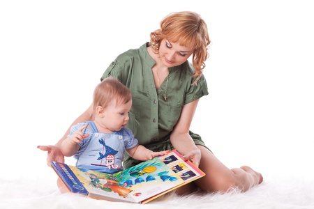 Mother with small baby reads the book on a white background. photo