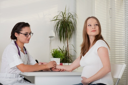 The doctor takes blood from a vein from the pregnant woman photo