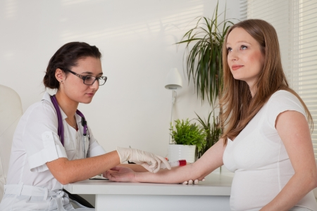The doctor takes blood from a vein from the pregnant woman